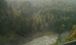 A fine mist hangs in the air over the Snoqualmie River below the falls.