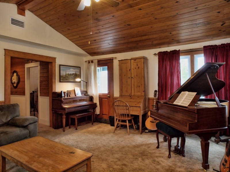 Yes, there are two pianos in this living room.  It's that big.  And tongue 'n groove red pine planks on the vaulted ceiling.