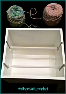 A ribbon storage box turned yarn slave.